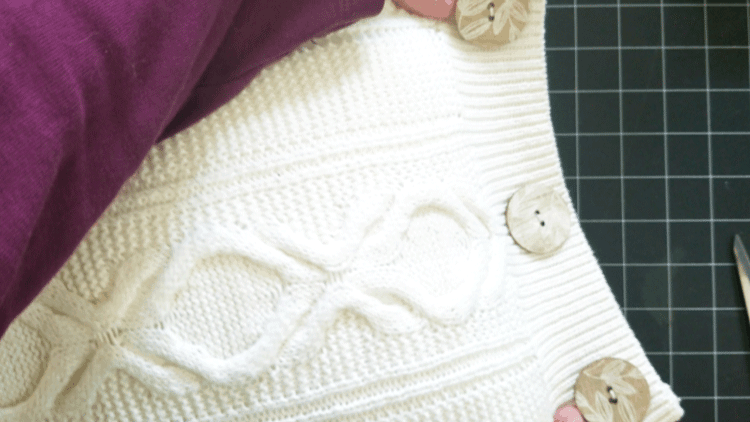 Adding the wood buttons to the side of a white sweater pillow