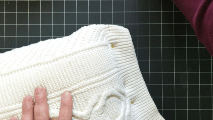 Pinning the edge of the white sweater pillow in order to add wood buttons to the side.