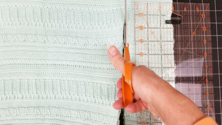 Cutting a sweater to make a cozy sweater pillow.