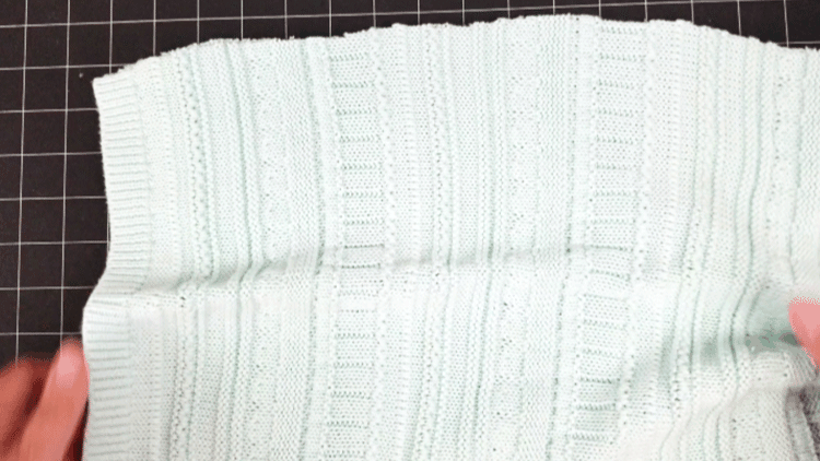 Turning the stitched sweater pillow inside out for finishing.