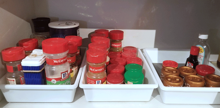 Drawer organizers used to organize spices in the kitchen cupboard
