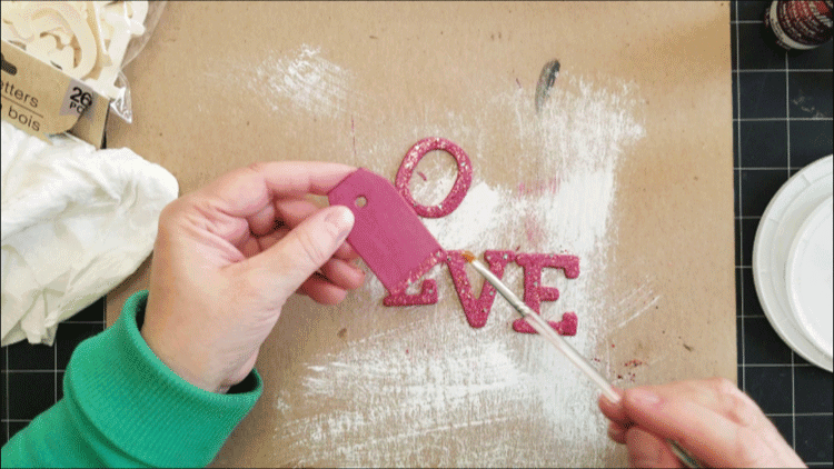 Adding a row of glitter paint to the bottom of the painted wood tag.