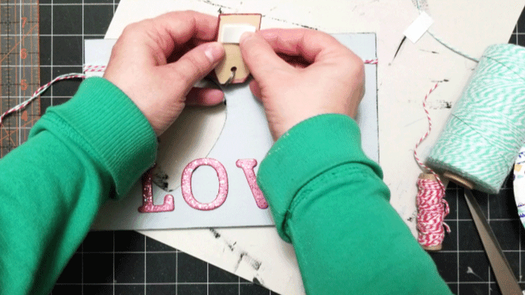 Adding foam mounting tape to the back of the painted wood tag to adhere it to the wood frame.
