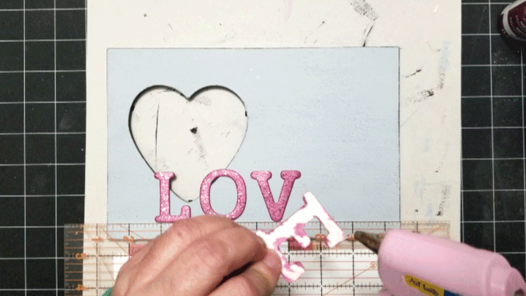 Adding hot glue to the back of the letters that spell out LOVE.