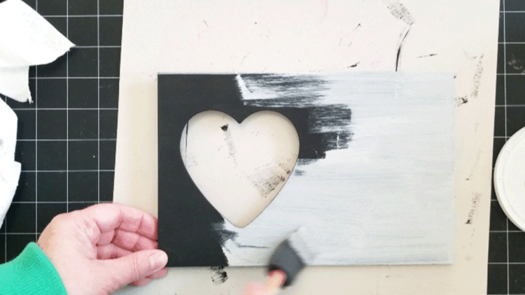 Painting the gray paint over the black paint on the wood frame.