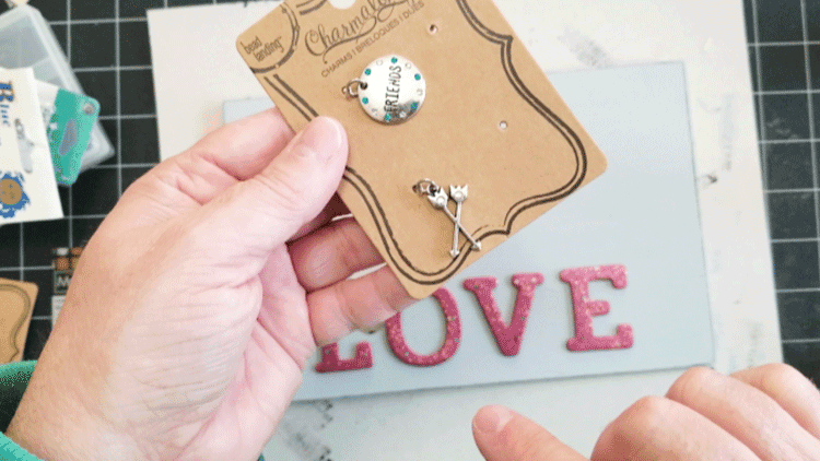 Choosing a silver arrows charm to hang on the painted wood tag.