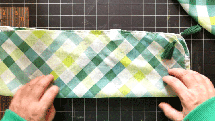 Folding a second scarf lengthwise to create a strap for the bag.