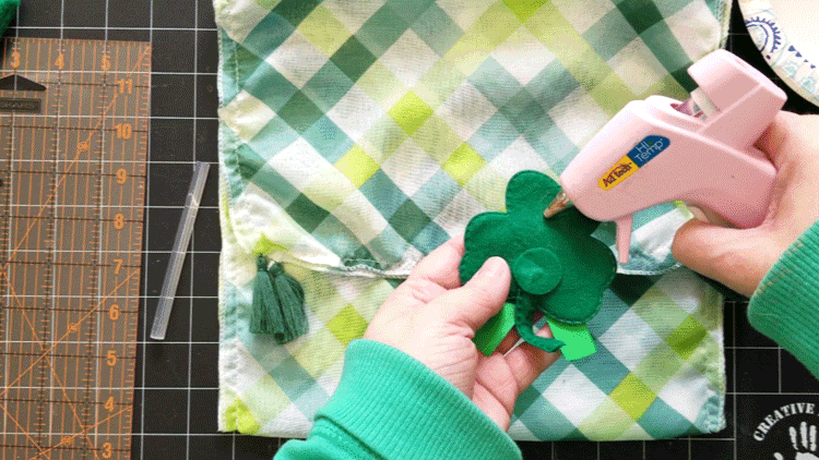 Using hot glue to attach the shamrock to the purse