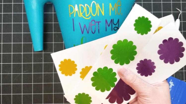 Adding vinyl flowers to the dollar tree watering can