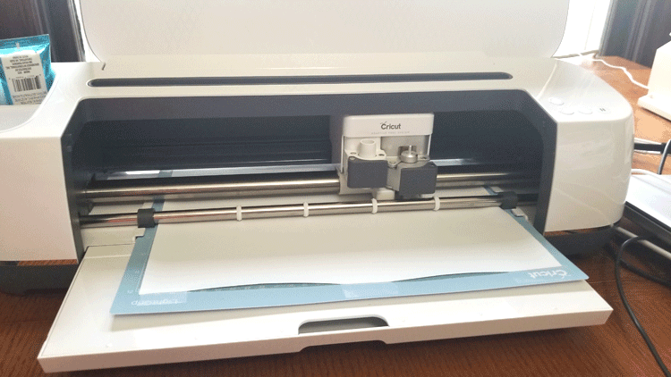 The Cricut Maker cutting out designs with white iron on vinyl.