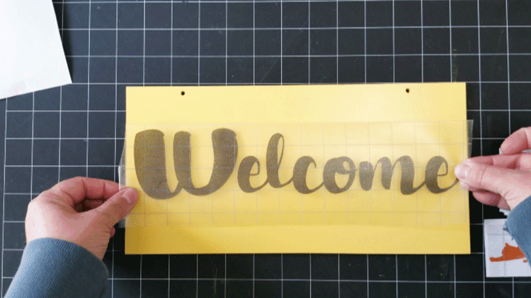 Placing the Welcome text on the sign with the transfer tape.