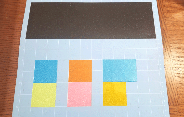 The different colors of transparent glitter vinyl laid out on the Cricut Mat ready to cut.