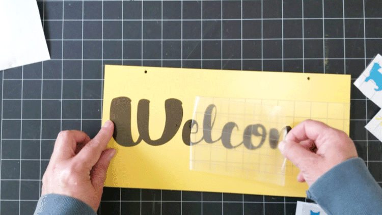 Removing the transfer tape from the Welcome text.