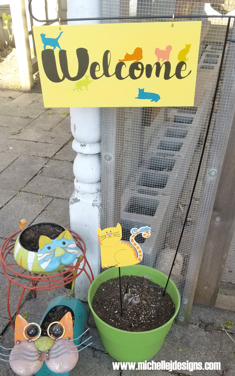 A custom welcome sign with script text and several cats.