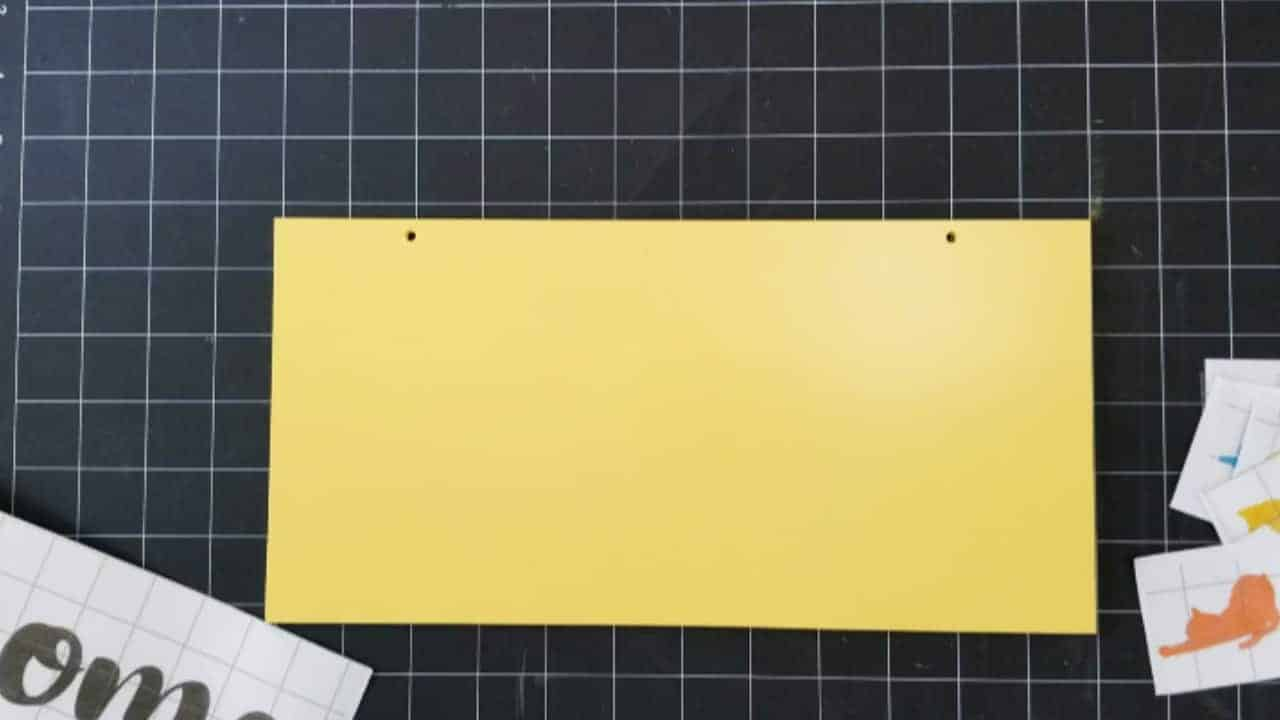 PVC tile cut to size with two holes drilled at the top and spray painted yellow.