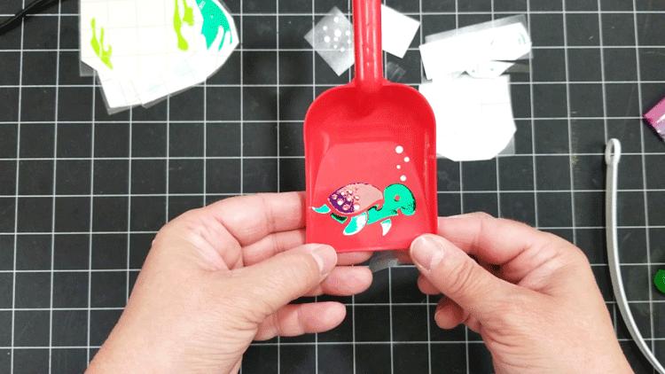 Finished multiple colored vinyl turtle design on sand shovel.