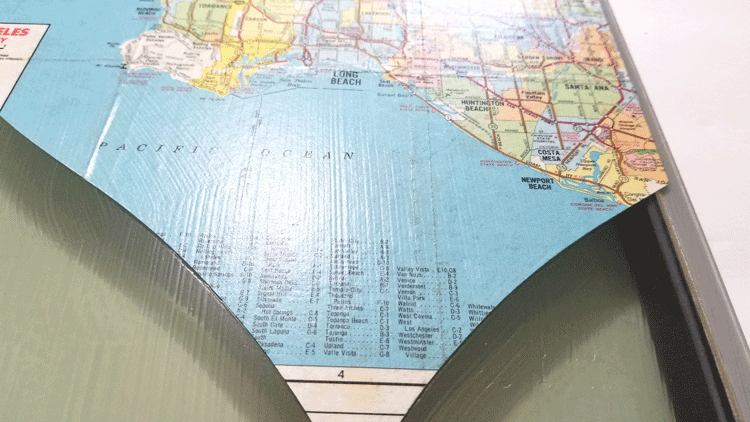 Using Mod Podge to adhere the map heart to the back of the glass tile.