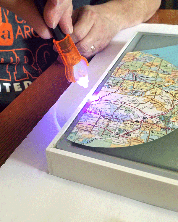 Using the light on the Bondic glue pen to dry the adhesive.