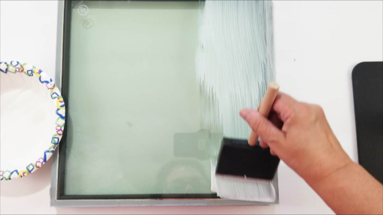 Brushing Mod podge all over the back of the glass tile.