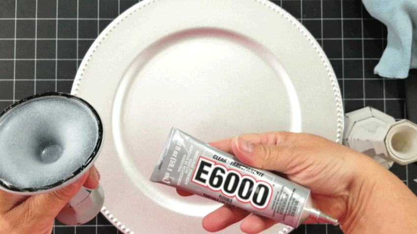 Adding one of the candlesticks to the charger plate with E6000 glue.