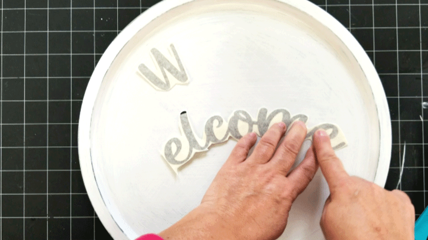 Adding the welcome text onto the pizza pan with brown vinyl