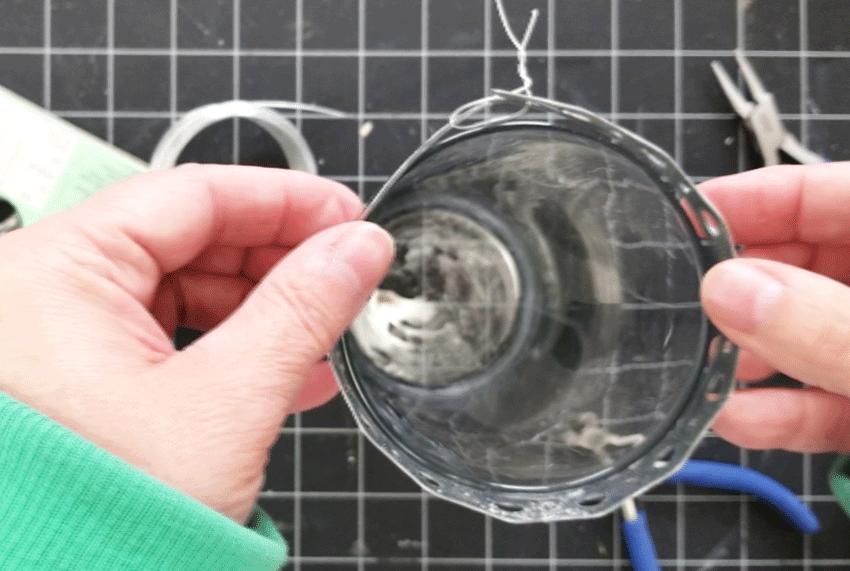 Sliding the metal piece onto the vase.