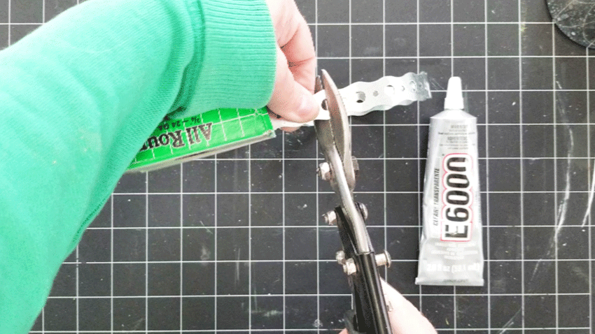 Using the tin snips to cut the metal to size.
