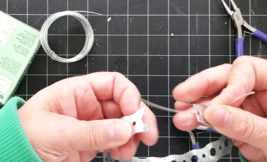 Threading the wire through the holes at the end of the metal bands.