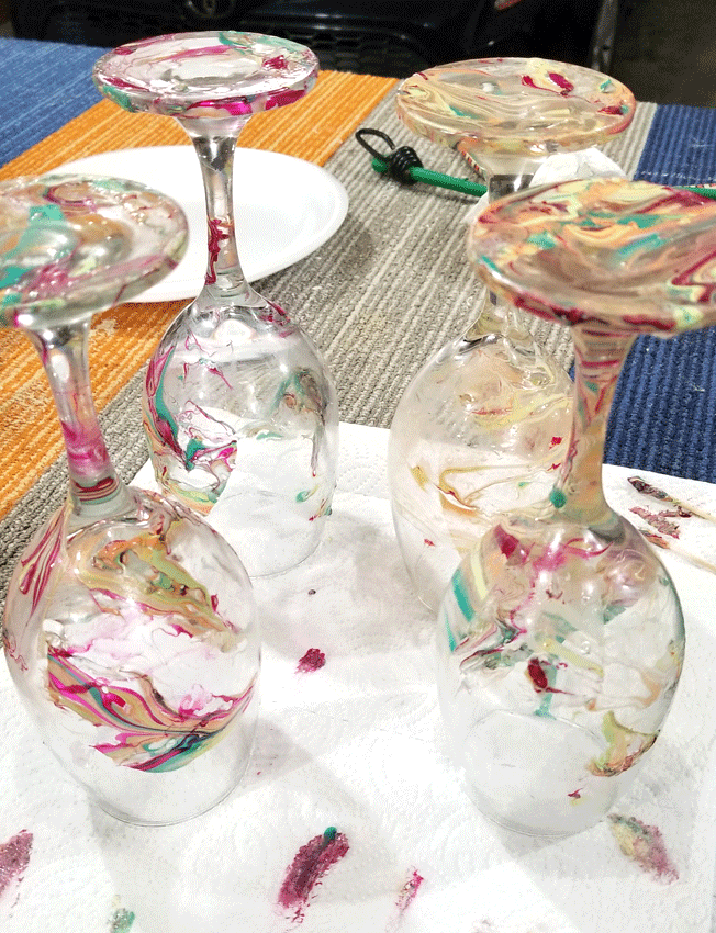 Upside down glasses drying after being dipped into water with nail polish.