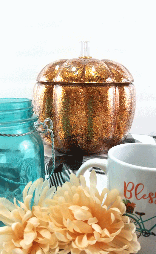 Finished glitter orange glass pumpkin with buffalo check and teal.  The perfect fall decor.