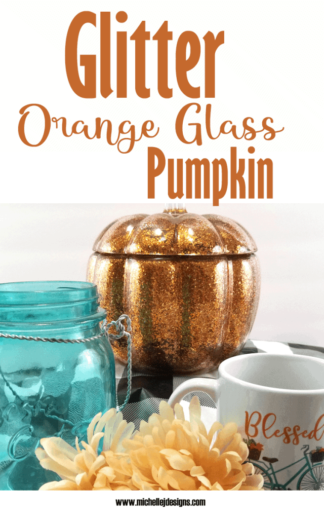 Finished glass pumpkin displayed with teal and orange decor.