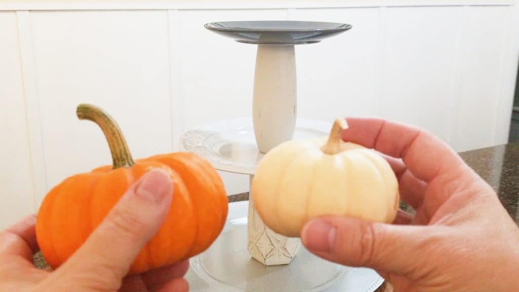 Mini pumpkins, one white and one orange that will be added to the tiered tray decor