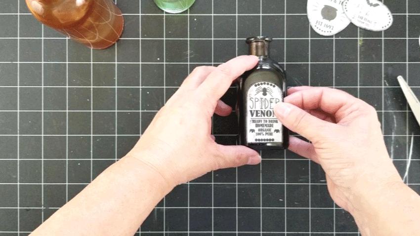 Adding the spider venom label to the purple bottle.