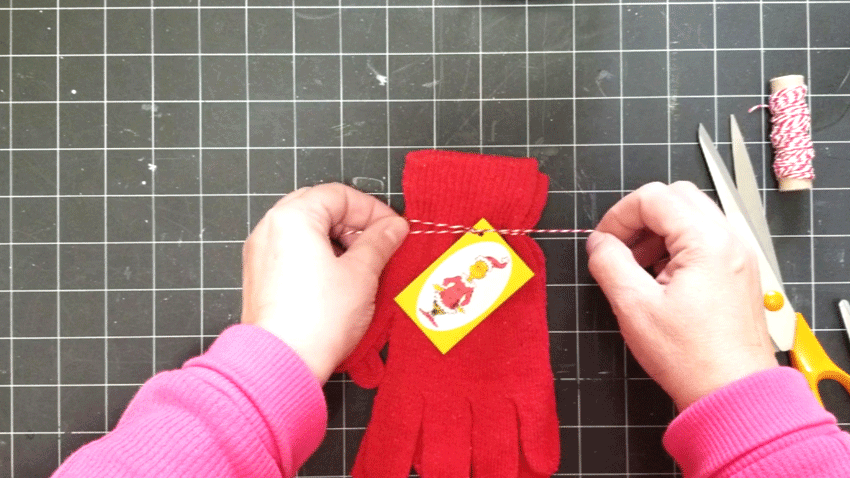 Adding a Grinch tag to the red gloves that will be placed in the gift jar.