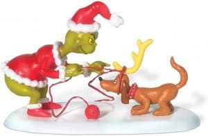 Dept 56 figurine of the Grinch tying the reindeer horn onto Max's head.