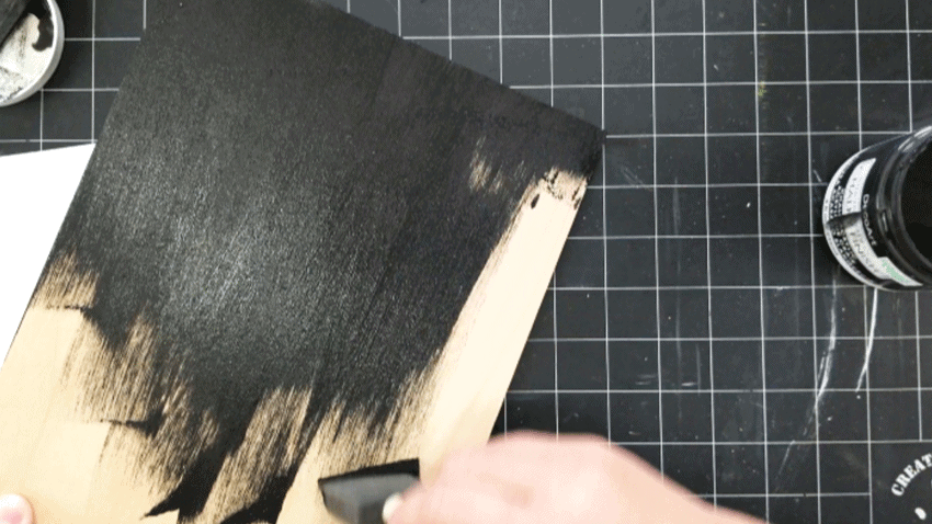 Painting the wood board with black chalk paint.- first coat