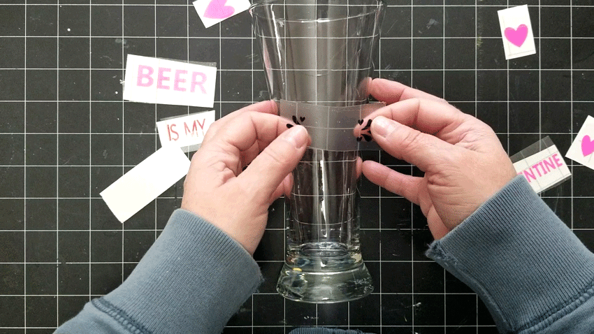 Adding the vinyl to the drinking glasses in sections starting with the center section.