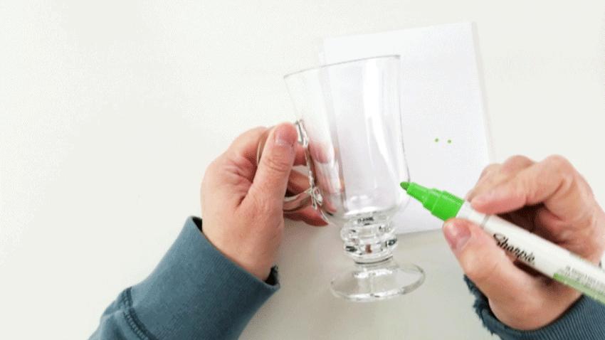 Using the paint pen to create shamrocks on the mug.