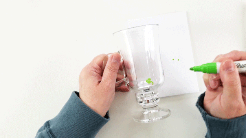 Adding shamrocks to the glass much by drawing them with a green oil based sharpie marker