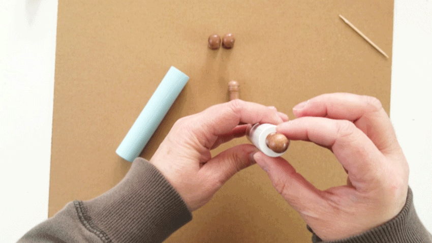 Adding the stained handle piece to the end of the painted dowel to form rolling pin handles.