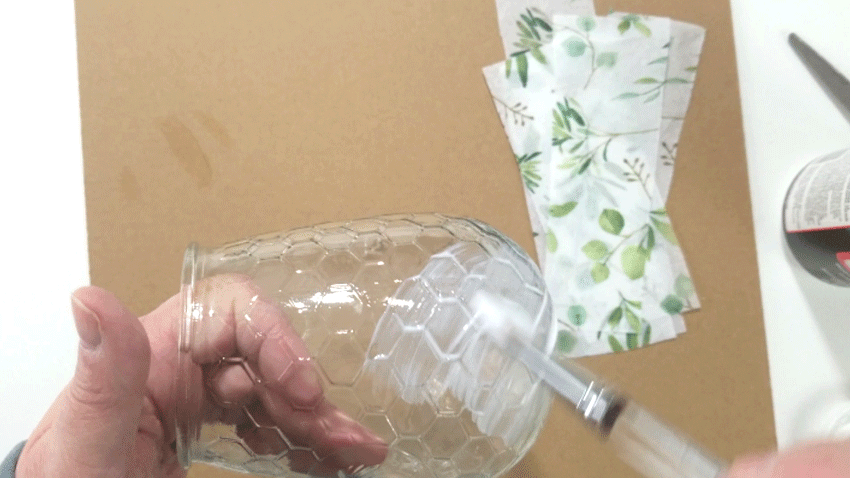 Applying the Mod Podge to the glass candle holder to add the tissue paper.