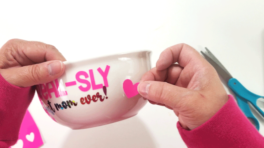 Adding color changing vinyl hearts to the text design on the bowl.