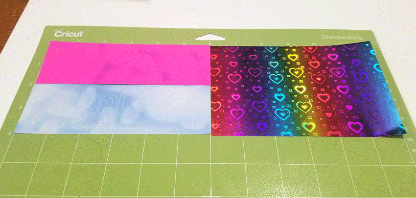 Color changing vinyl and rainbow heart vinyl on the Cricut mat.