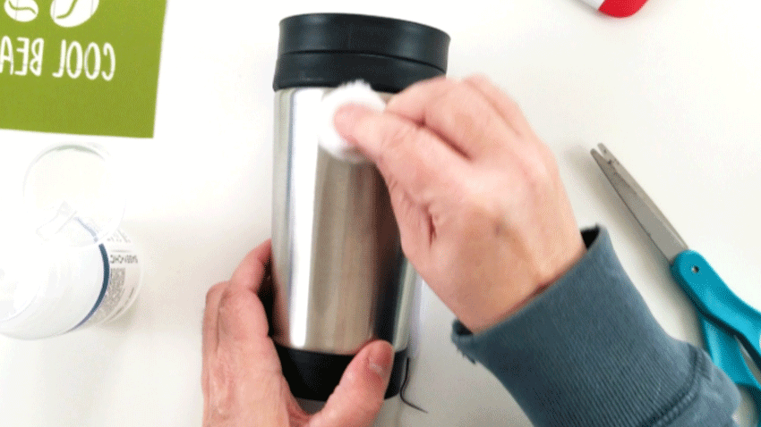 Cleaning the surface of the coffee travel mug with nail polish remover and a cotton ball.