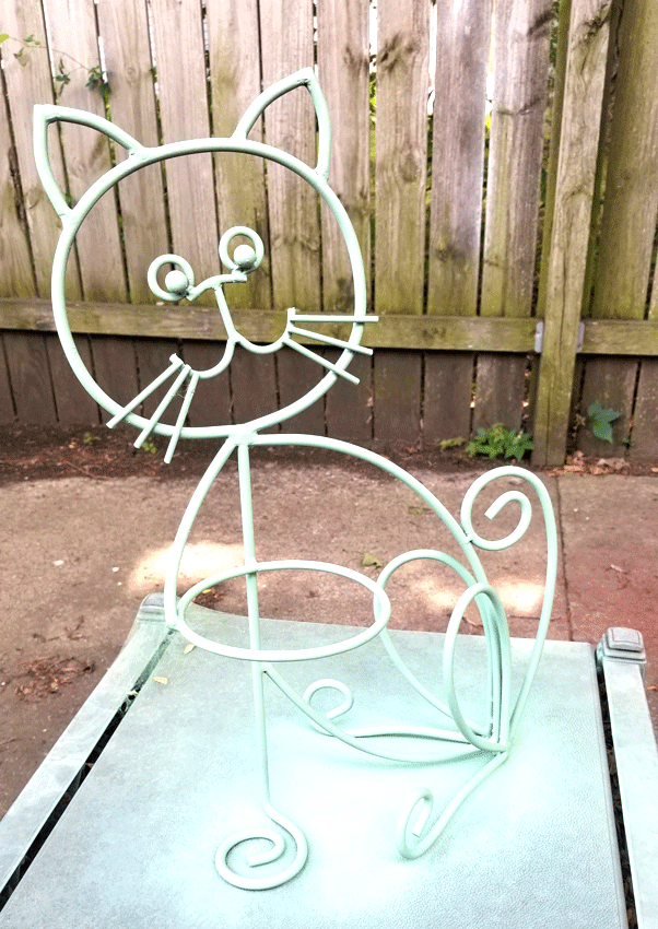 The metal outline of a cat planter spray painted with the Krylon Pistachio color.