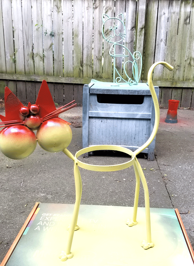 Painting two colors on this cat planter.  Paprika on his face and upper cheeks and yellow on his lower face and body.