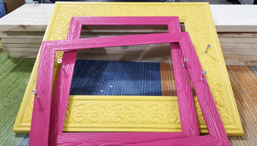 Pink and yellow frames with the screws ready to be hung on the fence.
