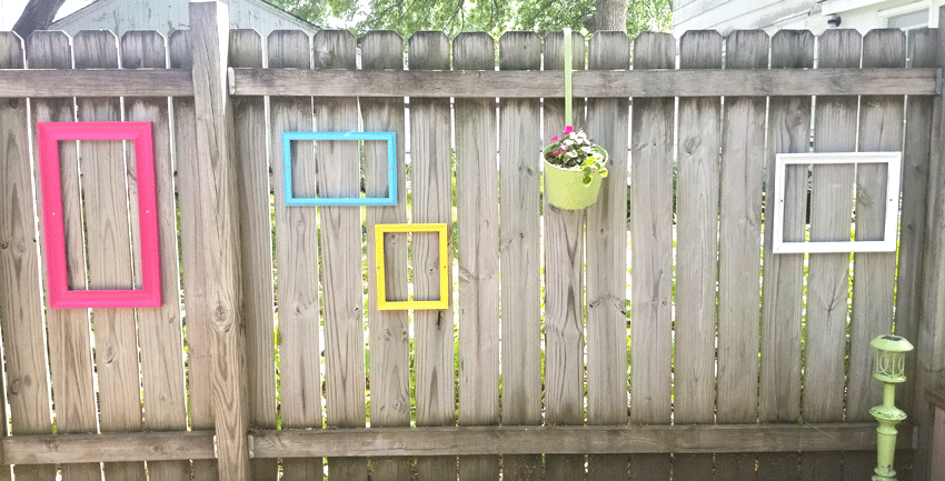 A section of fence with pink, teal, yellow and white frames