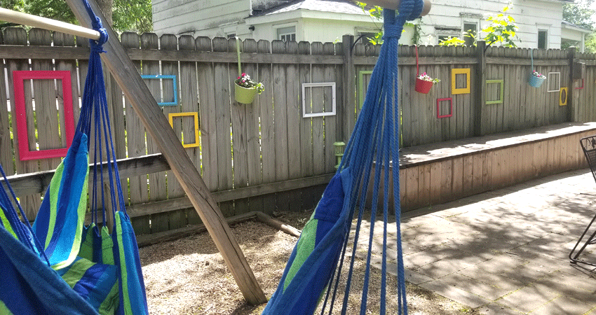 The finished fence with the hammock chairs.