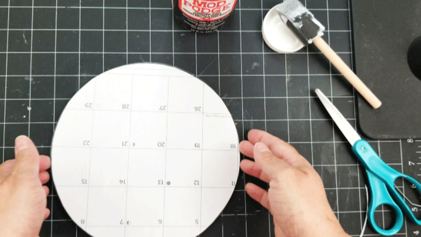 Placing the cut calendar page onto the Mod Podge on the underside of the glass cutting board.